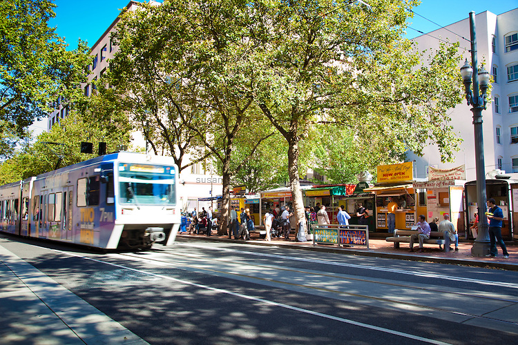 A sunny lunch time at the Food Carts in downtown Portland on SW 5th Ave. between Stark and Oak feature a variety of cuisines from Thai to Indian to Burgers to Soup.